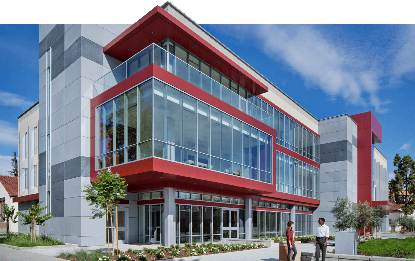 Large office building exterior, gray walls with red trim and floor-to-ceiling windows