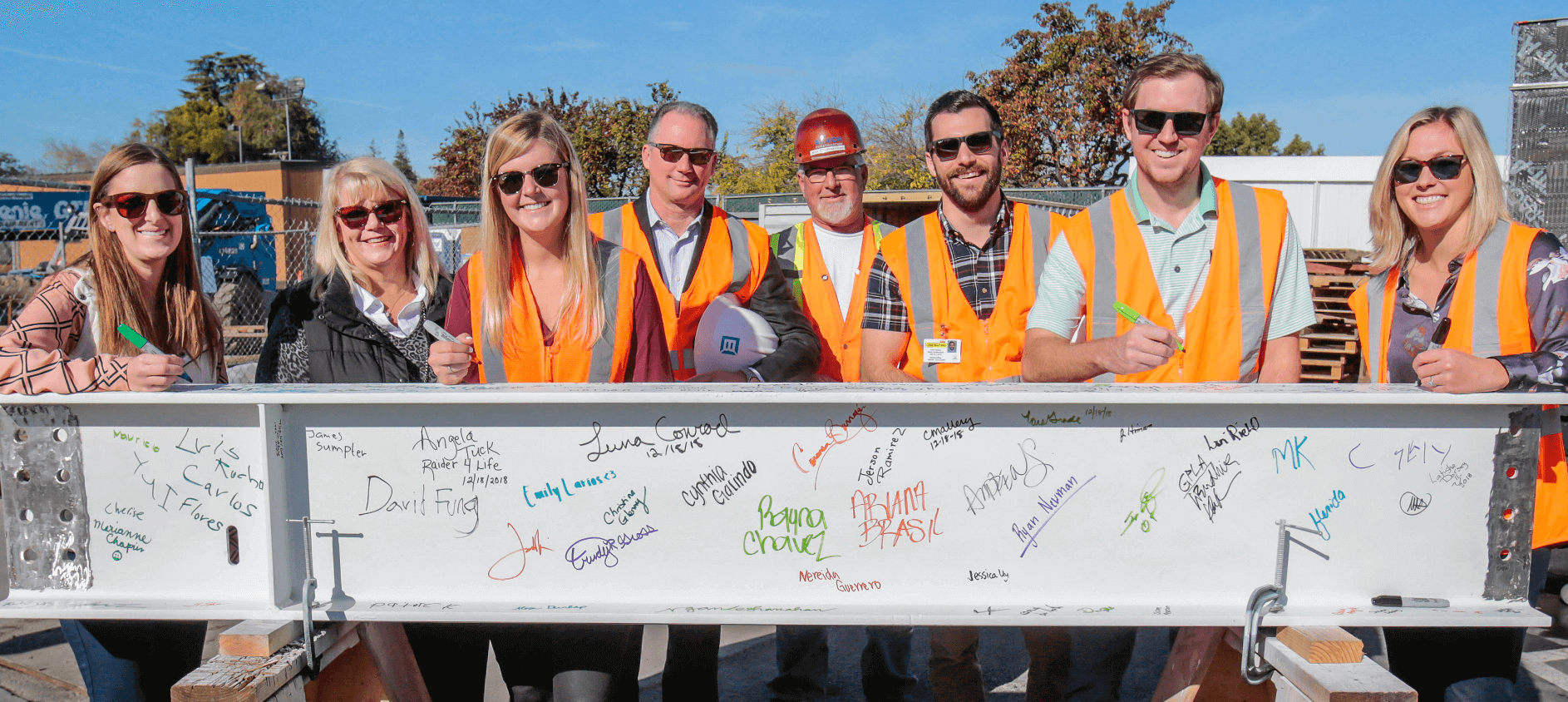 Blach construction employees beam signing